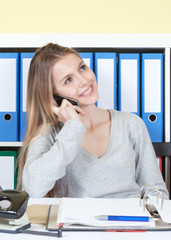 Lachende junge Frau im Büro am Handy