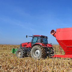 A tractor with a trailer to transport the grain to harvest corn.