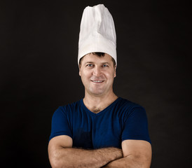 charming chef posing on black background