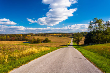 Country road and view of rolling hills and farm fields in rural