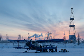 Biplane next to oil derrick on winter sunrise background