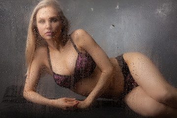 Beautiful blonde in lingerie behind wet glass