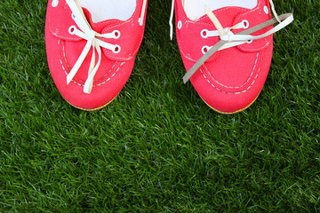 top view of red worn girl shoes over grass textured background