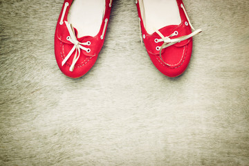 top view of red worn woman shoes over wooden textured background
