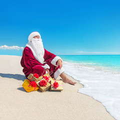 Santa Claus with many christmas golden gifts relaxing at tropica