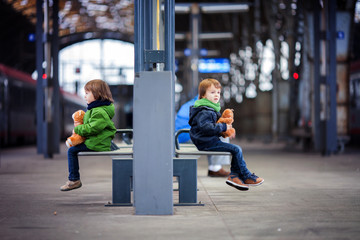 Two boys, sitting in a bench on the railway station