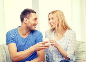 smiling man giving cup of tea or coffee to wife