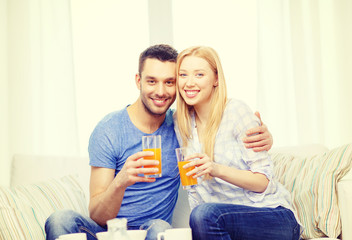 smiling happy couple at home drinking juice