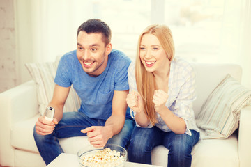 smiling couple with popcorn cheering sports team