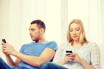 concentrated couple with smartphones at home