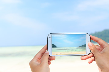 close up hand use smart phone take photography the beach