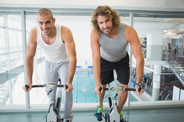 Fit men working on exercise bikes at gym