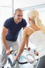 Smiling couple working on exercise bikes at gym