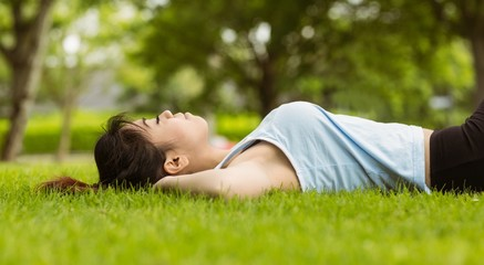 Healthy woman lying on grass in park