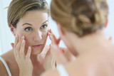 Middle-aged woman applying anti-aging cream - 75069052