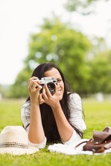 Smiling brunette lying on grass taking picture
