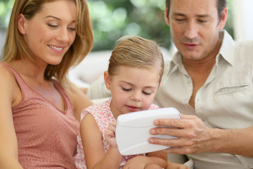 Parents with little girl playing with children's tablet