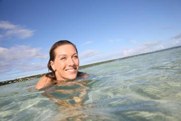 Portrait of smiling woman enjoying swimming in lagoon