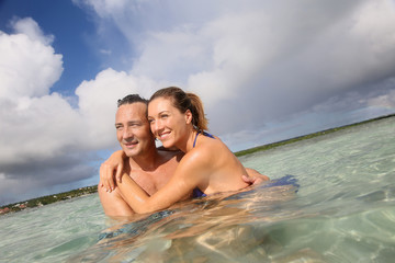 Cheerful middle-aged couple embracing in the sea