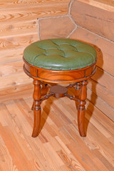 The stool with a leather upholstery stands near a timbered wall