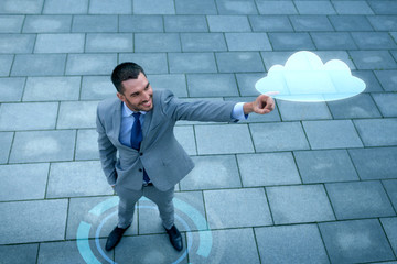 smiling businessman with cloud projection outdoors