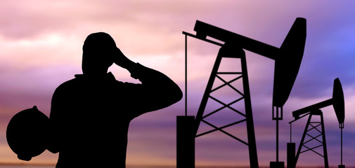 black silhouette of oil worker and pump jack
