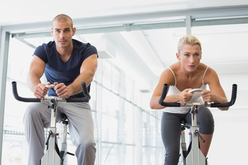 Determined fit couple working on exercise bikes at gym