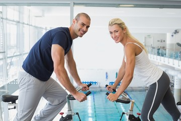 Side view of smiling couple working on exercise bikes at gym