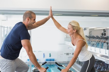 Fit couple giving high five while working