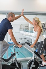 Couple giving high five while working on exercise bikes at gym