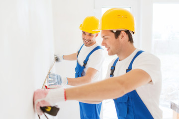 smiling builders with measuring tape indoors