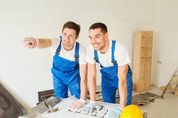 smiling builders with blueprint