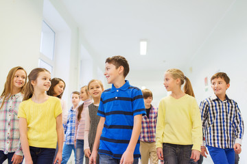 group of smiling school kids walking in corridor