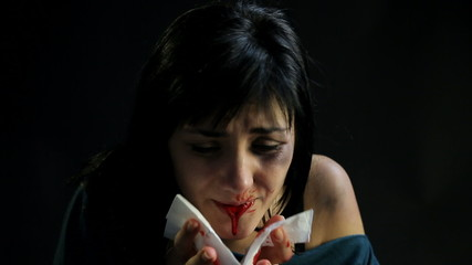 Woman spitting blood after being abused domestic violence