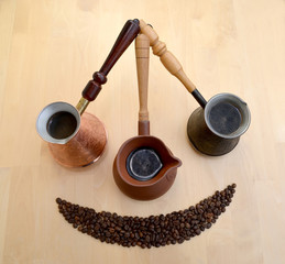 Metal and ceramic Turks about coffee and coffee grains on a ligh
