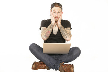 Junger mit Laptop ist überrascht