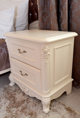Bedside table of color of an ivory in a bedroom. Modern classics