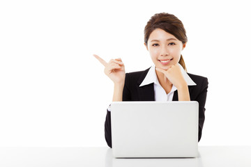 smiling young business woman working with  laptop and pointing
