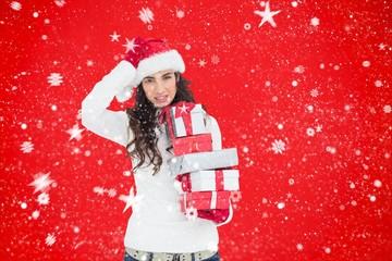Composite image of stressed brunnette in santa hat holding gifts