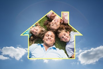 Composite image of happy family lying on the grass in a circle