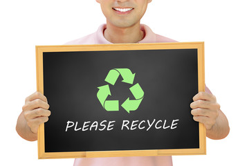 Recycle sign with texts on blackboard held by smiling man