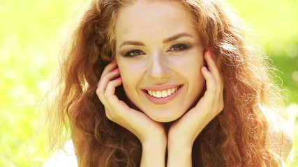 Beauty girl with healthy long curly hair outdoors. Happy smiling