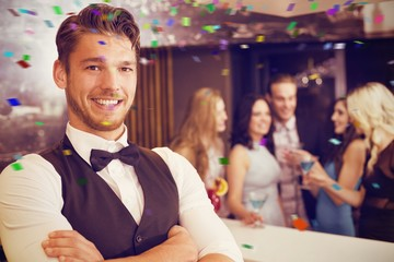 Composite image of handsome barman smiling at camera