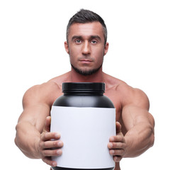 Serious muscular man holding holding jar with protein