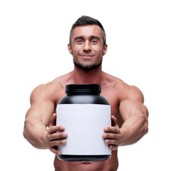 Happy muscular man holding holding jar with protein