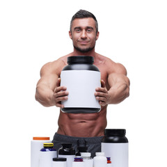 Portrait of a happy muscular man with sports nutrtion