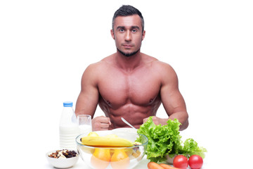 Happy muscular man sitting at the table with healthy food