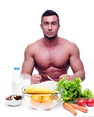 Muscular sports man sitting at the table with healthy food