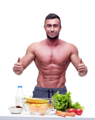 Happy muscular man standing with thumbs up and healthy food