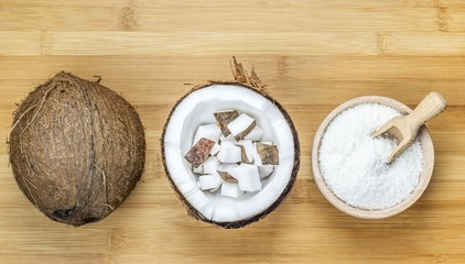 Bowl of desiccated coconut whole and chunks on wooden background